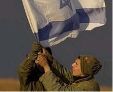 Soldiers Putting Up an Israeli Flag in a Staging Area near Gaza. (AP)