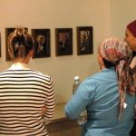 Women looking at Morya's Photographs