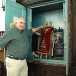 Louis Lipstein poses in front of the Aron Hakodesh